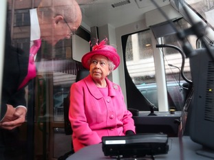 Queen Elizabeth II chats to senior driver Derek Taylor during a tour of a tram