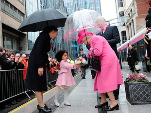 The Queen receiving flowers from a little girl at the tram stop on Bull Street