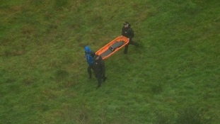Police officers carry an empty stretcher at one of the search sites.