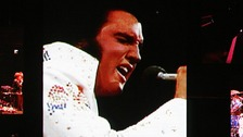 A live band backs up a virtual Elvis during a memorial concert of Elvis footage