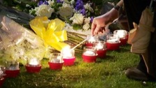 Candles being lit at the memorial on the 40th anniversary.