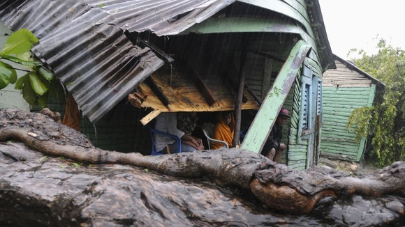 A family sits in their porch after winds from Tropical Storm Isaac brought a tree down, hitting the corner of their house, in El Habanero