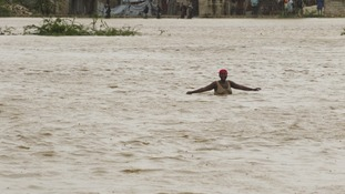 A woman wades through floodwaters in Port au Prince