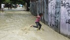 A child runs through floodwater from Tropical Storm Isaac in Vicente Noble