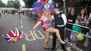One of the dancers with a police officer takes part in the Notting Hill Carnival in west London.