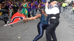 Police Sergeant Siobhan Elliot dances with revellers at the Notting Hill Carnival in west London.