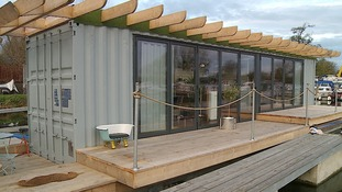 A floating home created from a metal shipping container.