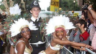 Policeman with performers during the Notting Hill Carnival, London.