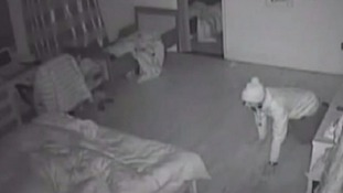 Armed burglar caught on camera crawling into sleeping couple's bedroom