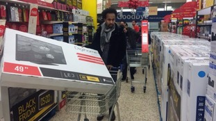 Customers at Tesco get their hands on discount televisions.