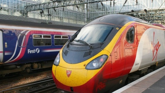 A First service passes a Virgin Pendolino train in Glasgow Central Station.
