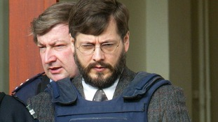 Belgian convicted child rapist Marc Dutroux leaves court escorted by police officers in 2003