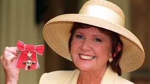 Black poses with her OBE in 1997
