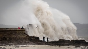 People watch waves close to the harbour wall at Porthcawl, South Wales, as Storm Desmond hits the UK.