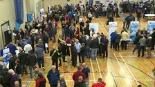 Crowds of people at a jobs fair in a sports hall.
