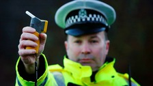 A police officer presents a breathalyser