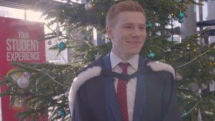 Watmore standing in front of a Christmas Tree in his graduation gown