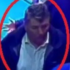 CCTV image of a man in a white shirt. He is highlighted with a red circle