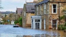 A pub with water levels up to the windows. A car in the street is almost entirely covered.