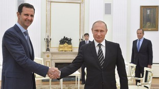 File photo of Putin and Assad shaking hands