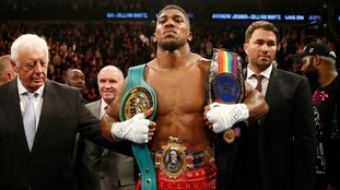 Anthony Joshua celebrates with the belts after winning the fight