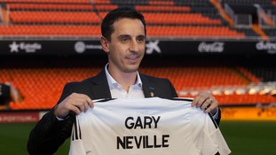 Neville poses for photographs during his unveiling as Valencia coach.