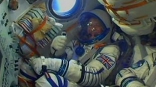 Tim Peake offers thumbs up from inside the Soyuz space capsule.