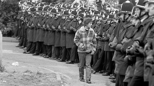 A protester walks in-front of a police line in 1984