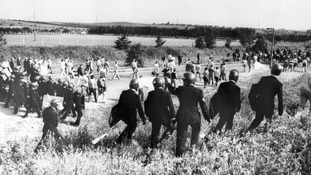 Police in anti-riot gear escort picketers away from their position near the Orgreave Coking Plant near Rotherham.