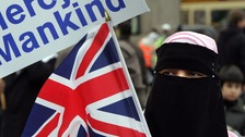 A Muslim waves a British flag at the Islamaphobia rally.