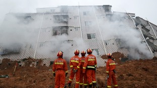 Firefighters look on as smoke rises in front of a damaged building at the site of a landslid