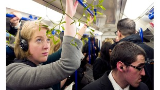 Londoners bring Christmas cheer to the tube with mistletoe