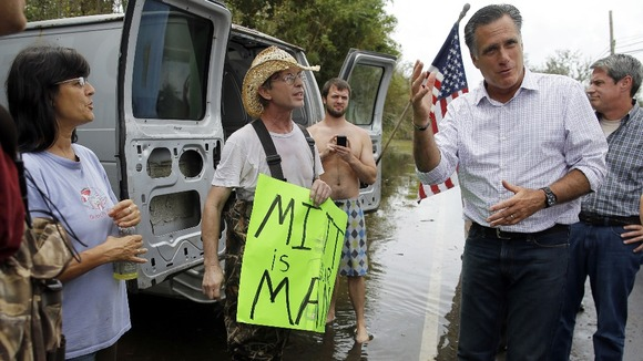 Mitt Romney talks to people on the side of the road while looking at damage from Hurricane Isaac in Jean Lafitte