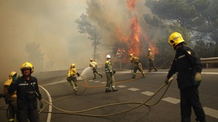Firefighters try to extinguish fire in forest on road between Marbella and Monda in Ojen