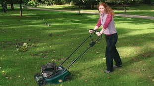 A woman mowing some grass