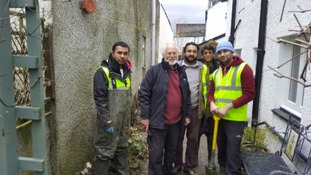 Volunteers with local people affected by flooding