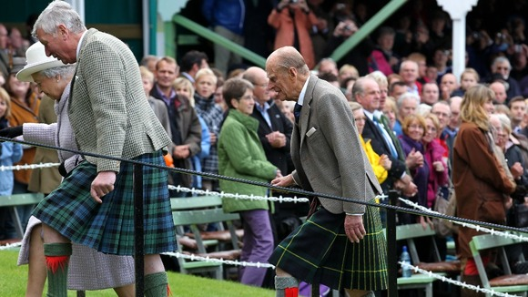 Queen Elizabeth II (left, partially obscured) accompanied by the Duke of Edinburgh (right) at the Braemar Gathering.