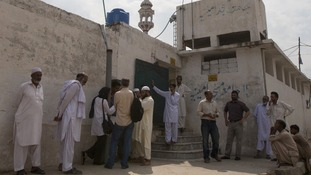 Residents and media gather outside a mosque near Rimsha Masih's home