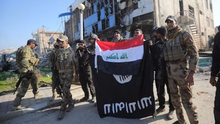 Iraqi soldiers pull down an Islamic State flag from a building in Ramadi