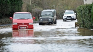 Cars drive through flood waters