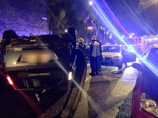 Dramatic photos show car flipped in high street crash.