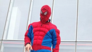 A person wearing a Spiderman fancy dress outfit.