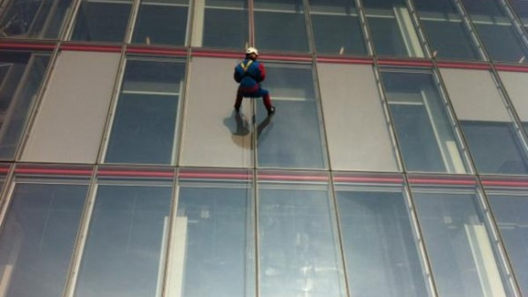 A person dressed in a Spider-Man outfit abseils down London&#x27;s Shard building.