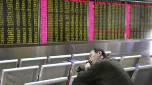 An investor in Beijing takes a nap in front of an electronic board showing stock information on the day the markets were shut early.