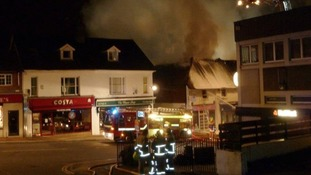 Firefighters stand back as the blaze is bought under control