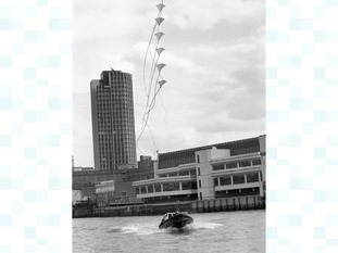Peter Powell controls seven of his stunter kites from a launch speeding towards Waterloo Bridge in 1976.