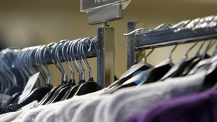 Clothes hang on a rail as sales dropped in August