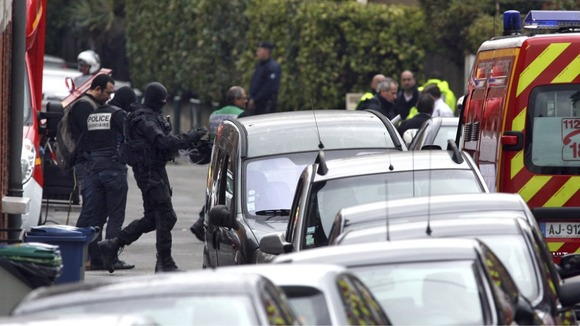 Masked French special unit policemen outside the Toulouse siege 