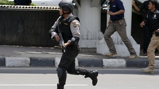 An armed officer runs after the blasts and gunfire.