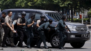Armed officers use a car for cover during the Jakarta siege.